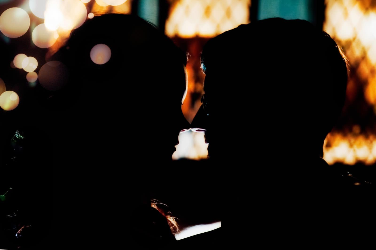 Silhouette of Bride and groom in front of a window after dark