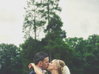 Bride & Groom kissing in front of a large tree