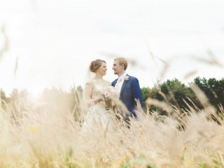 Bride and groom looking at each other whilst standing in a corn field