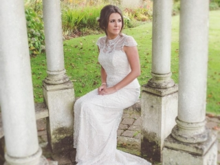 Bride sat on a stone seat with her hand in her lap looking of to the right