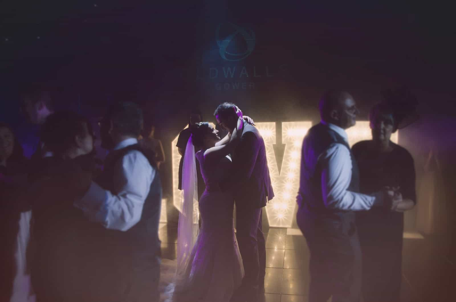 Bride & Groom stood on dance floor looking at  each other with guests dancing around them