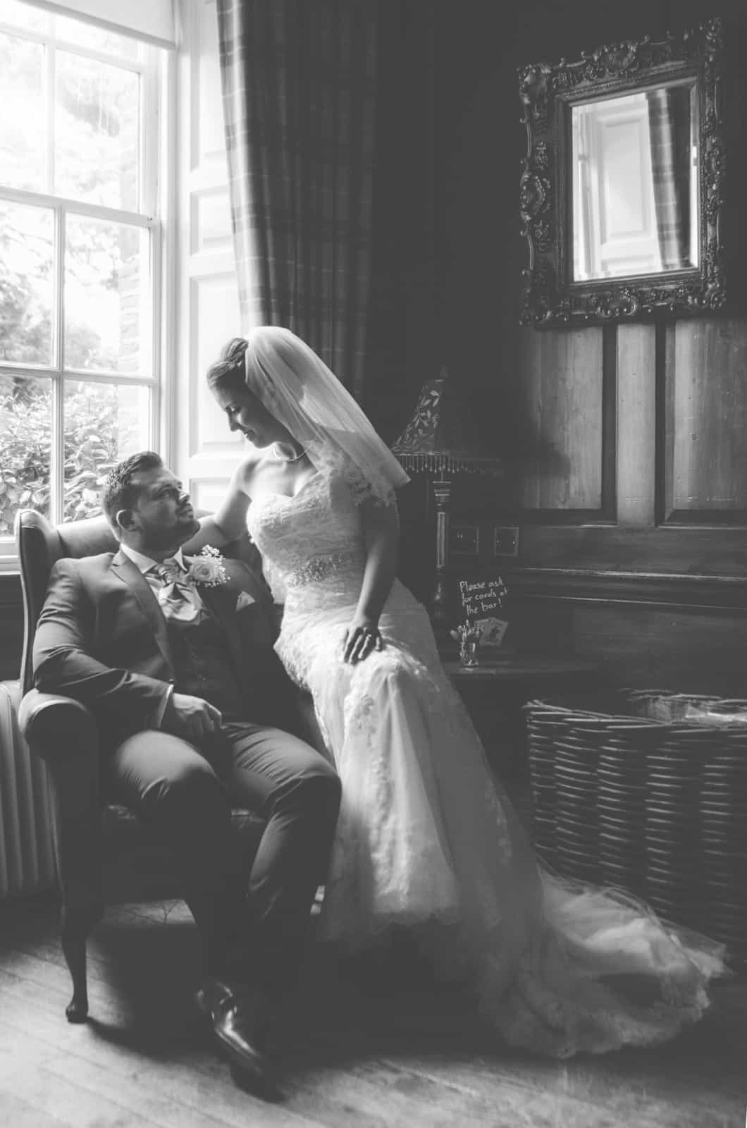 Groom sat on a leather chair in a wooden panelled room with bride sat on the arm of the chair looking at each other