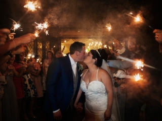 Bride & Groom kissing as wedding guests hold sparklers