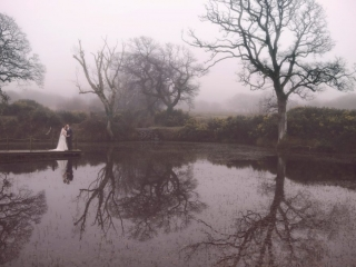 Bride & Groom stood on jetty overlooking a lake with trees reflecting in the water on a misty day