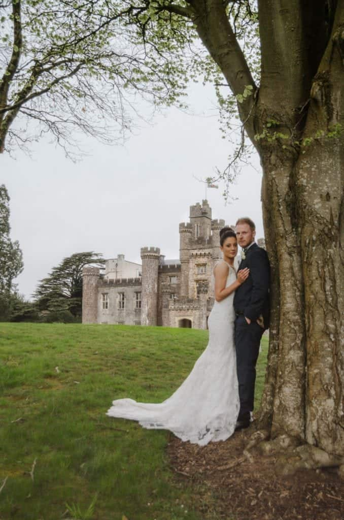 Bride & Groom stood leaning on a tree with a Hensol Castle in the background