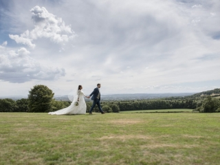 Bride & Groom walk across grass