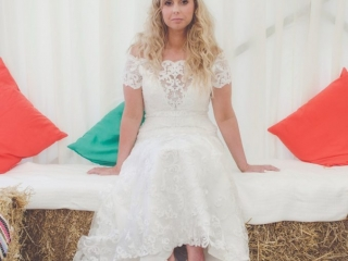 Bride sat on bail of hay in marquee