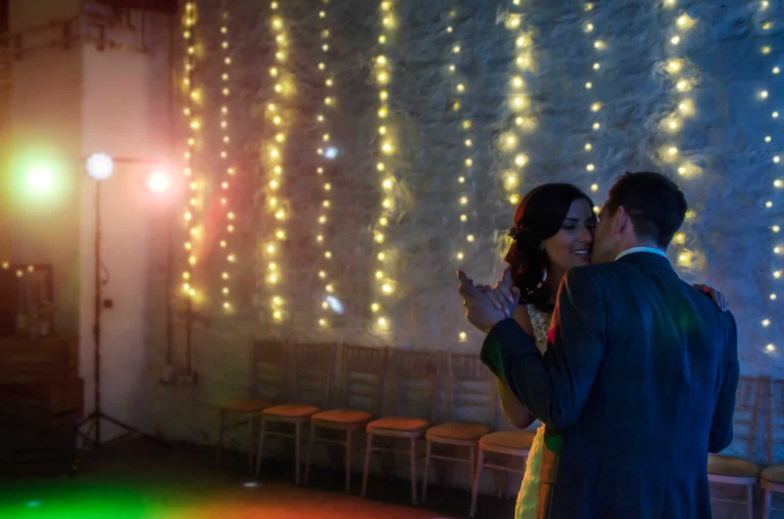 Groom kisses bride during first dance