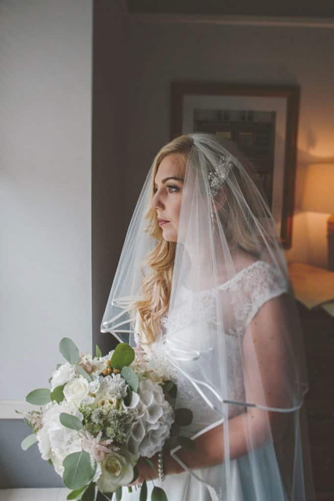 Bride stood by window holding her wedding bouquet