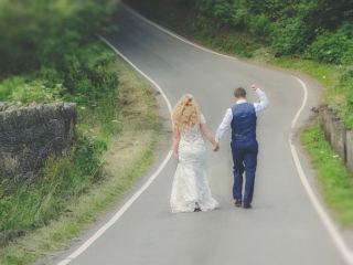 Bride & Groom walk down a country lane with groom raising arm in victory