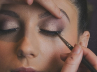 Bride with eyes closed having her wedding makeup applied