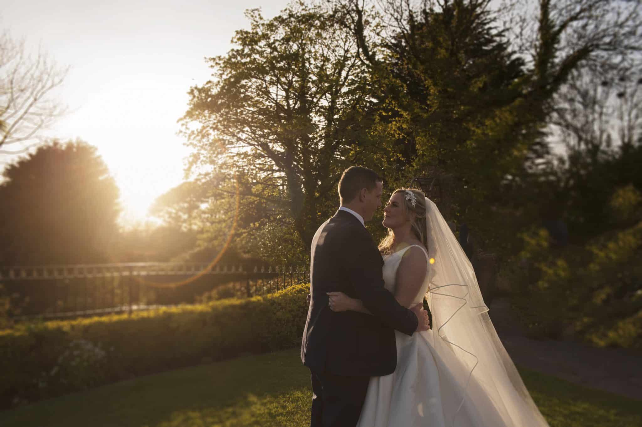 Bride & Groom stood in garden at sunset