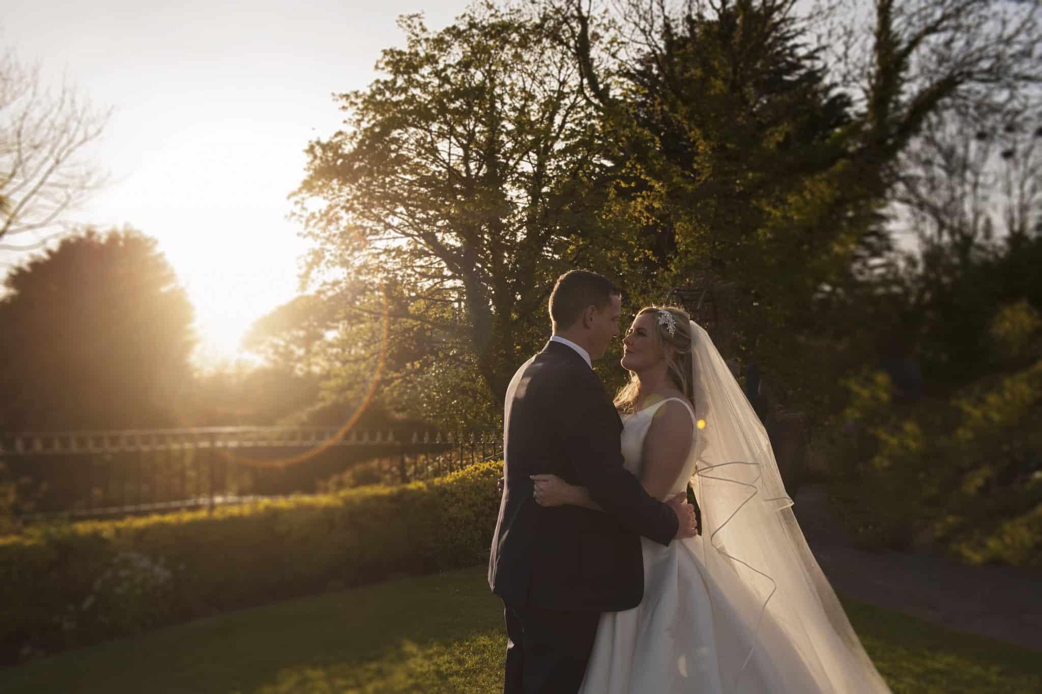 Bride & Groom stood in garden at sunset