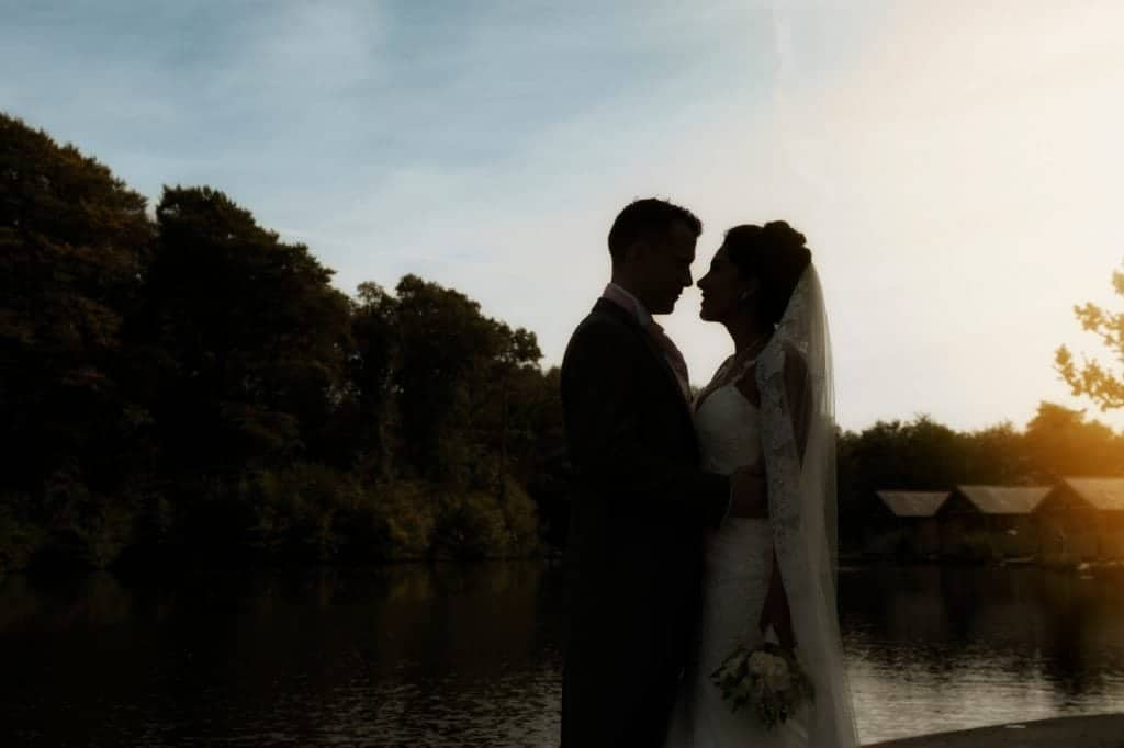 Silhouette of bride & groom stood in front of a  lake with cabins in the background at sunset