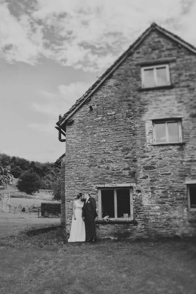 Bride & Groom stood against an old stone building kissing