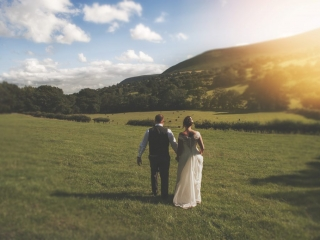 Bride & groom walk through field in sunshine wedding photographers cardiff