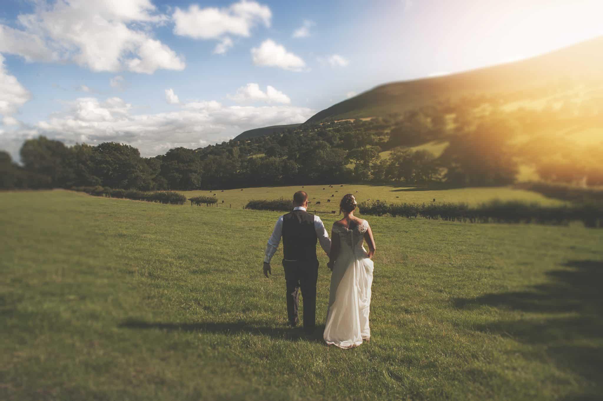 Bride & groom walk through field in sunshine