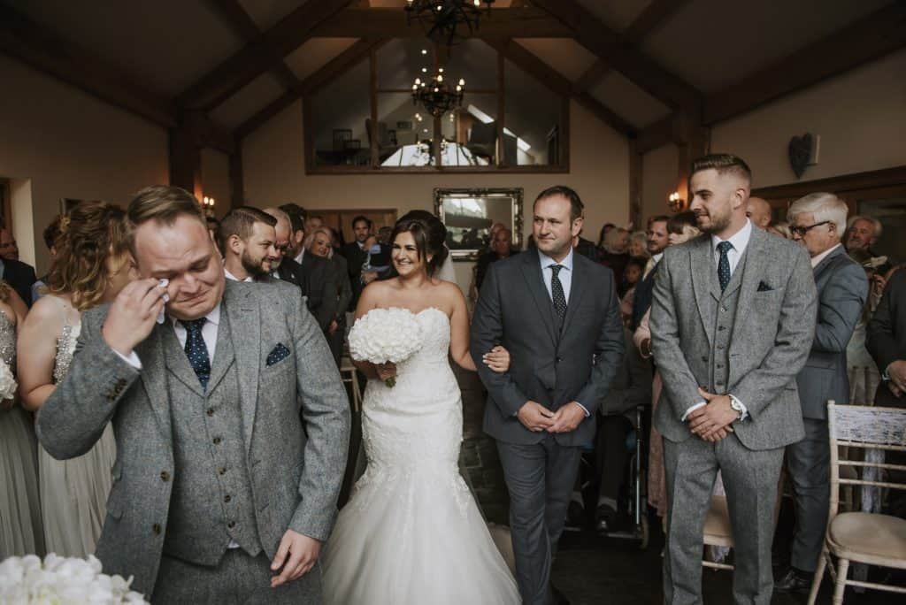 wedding photographers cardiff - Bride and father walk down aisle as groom cries