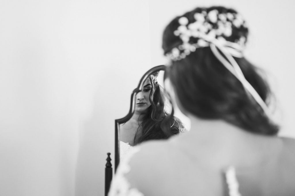 Bride stood looking in a mirror
