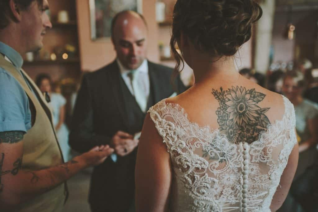 Close up of Bride's tattoo whilst stood at the alter saying her vows