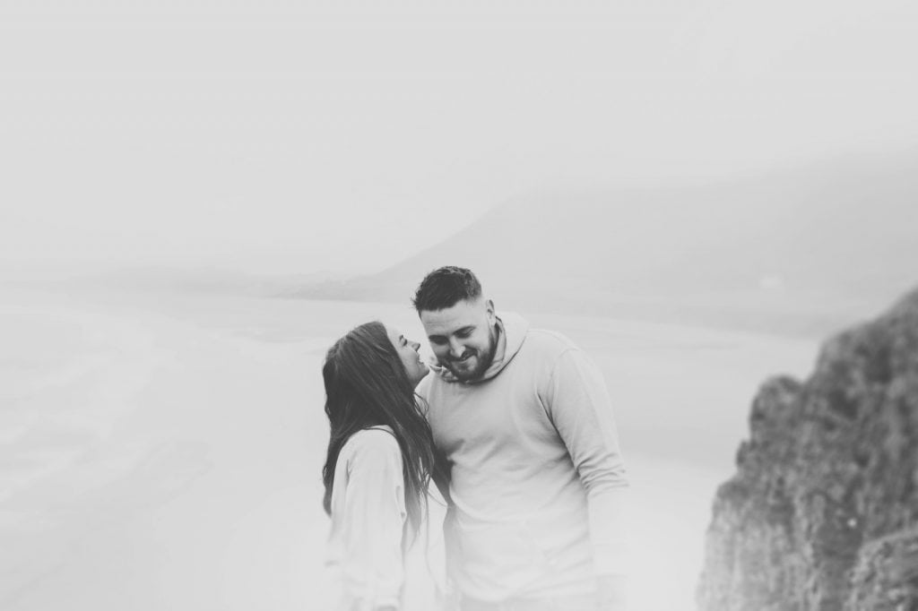 Couple whisper to each other on misty hilltop