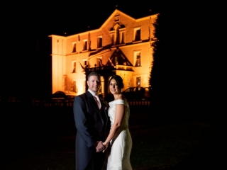 Bride and groom stood in front of Court Colman Manor after dark