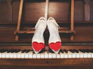 Pair of wedding shoes with red hearts resting on a set of piano keys
