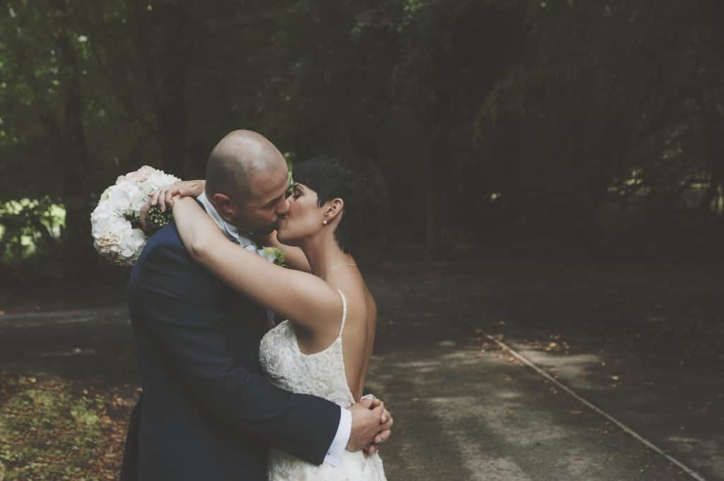 Bride & Groom kiss in pathway wedding photographers cardiff