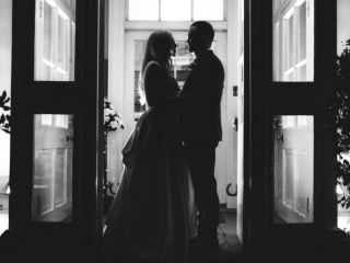 Silhouette of a couple stood in a door way