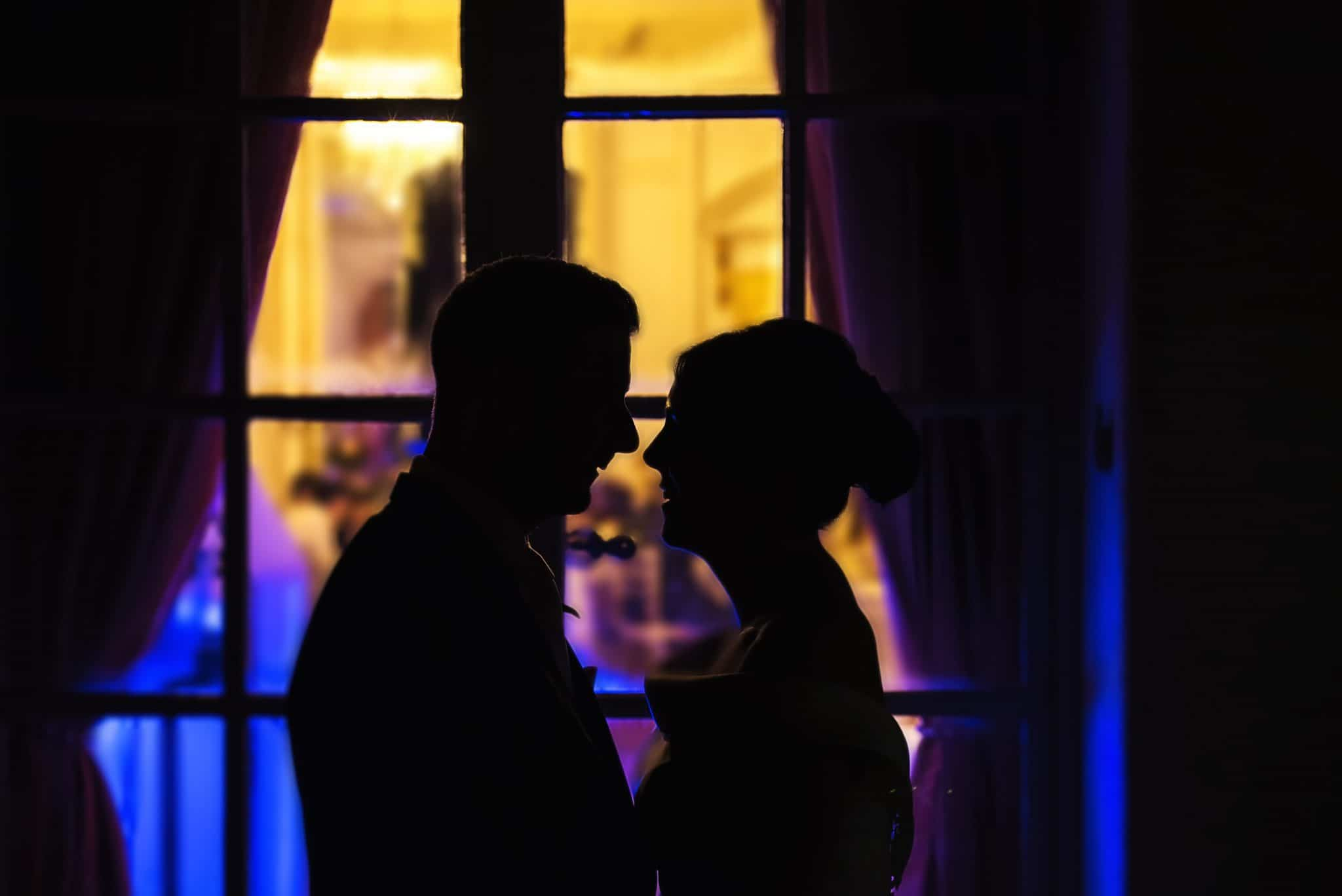 wedding photographers cardiff - Couple silhouetted against window