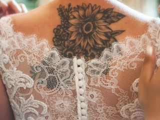 Close up of bride's back tattoo and wedding dress details