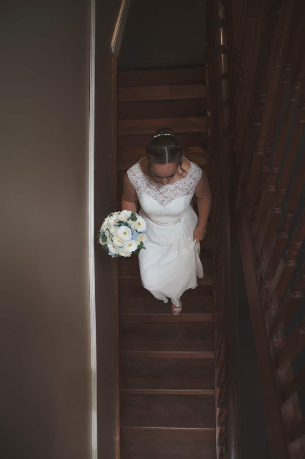 Over head shot of bride walking down a set of wooden stairs holding her wedding bouquet