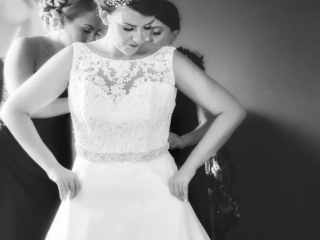 Bride stood with her hand on her hips whilst her bridesmaids adjust her wedding dress