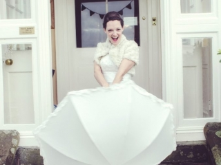 Bride stood on stone steps in red wellies with white polka dots holding a white umbrella