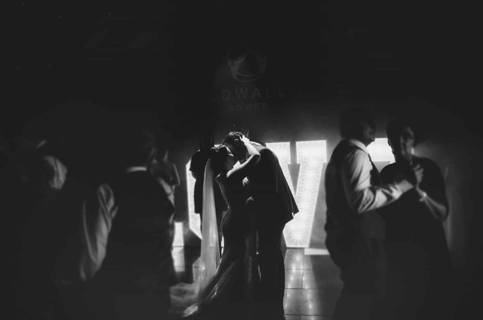Bride and groom stood on dance floor kissing during their first dance
