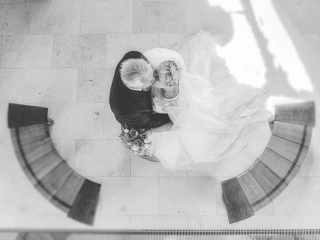 Over head shot of bride and groom kissing next to two semi circle benches
