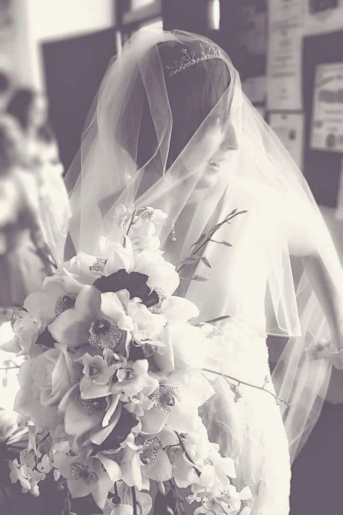 Bride looking over her shoulder holding wedding flowers