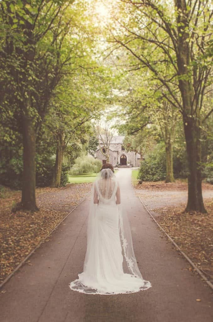 Bride stood facing back to us on a tree lined driveway