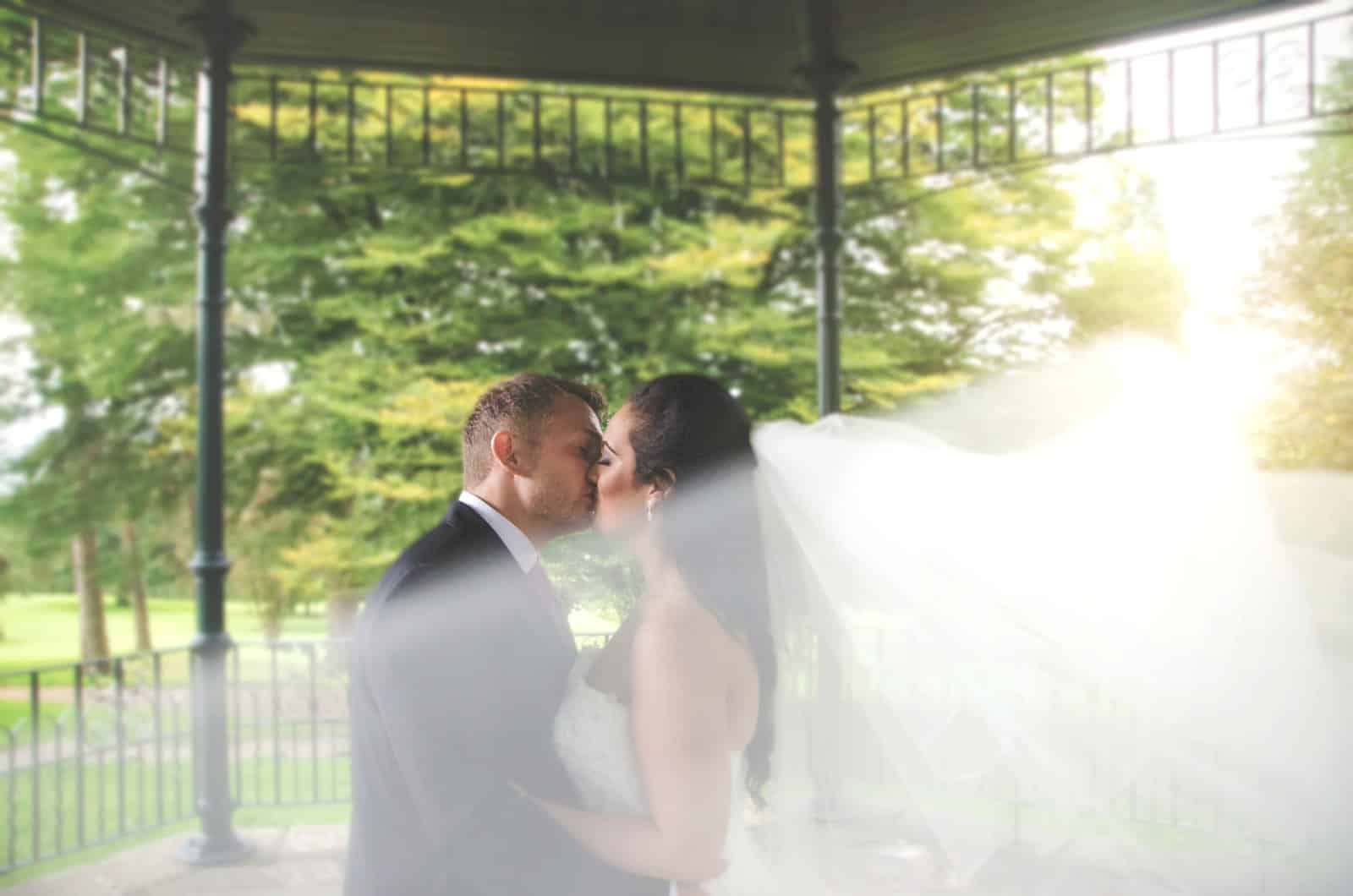 Bride & Groom Kiss in park with veil in foreground