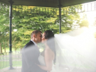 Bride and groom kissing in a pagoda with bride's veil in foreground