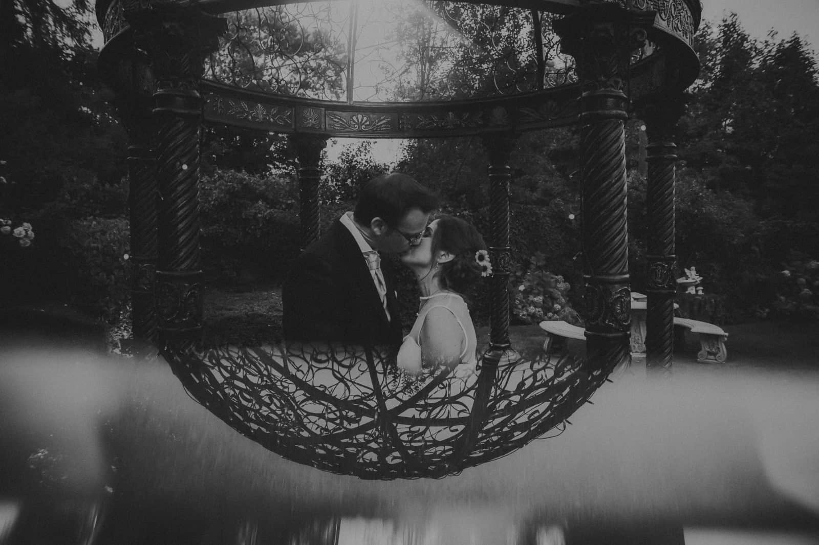Bride and groom kissing in front of bandstand with refection below