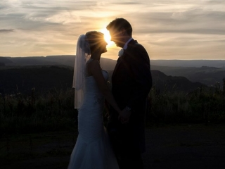 Silhouette of bride and groom facing each other with sun setting between them