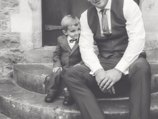 groom and page boy at on stone step in front of a wood door