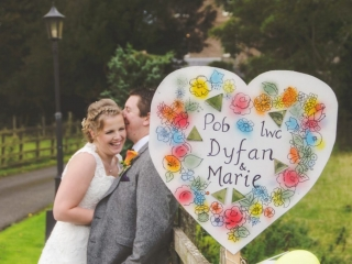 Bride and groom laughing behind a large heart shaped sign