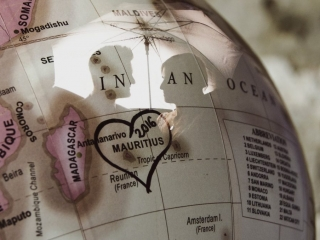 Double exposure for a couple on a globe with a heart around Mauritius