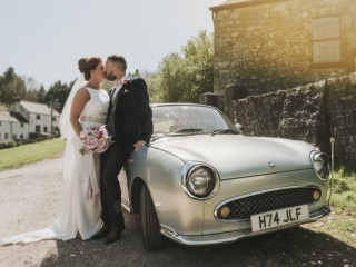 Bride & Groom kiss next to car wedding photographers cardiff