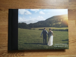 wedding album closed on a wooden floor with an image cover of a bride and groom walking across a field