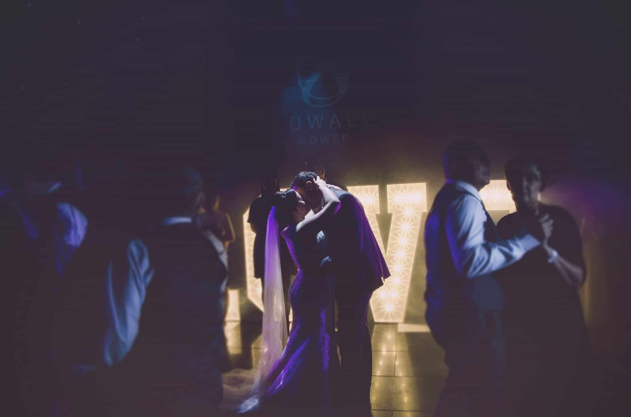 Cardiff wedding photographer - Bride & Groom kiss on a dance floor with a lit up love sign behind them