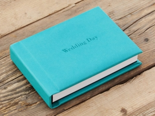wedding album closed on a wooden floor with a light blue leather cover reading Wedding Day