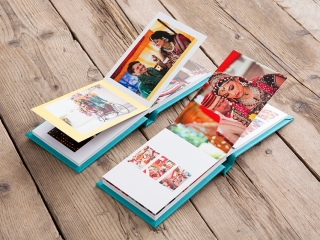wedding album open on a wooden floor with a light blue leather cover showing an Asian wedding
